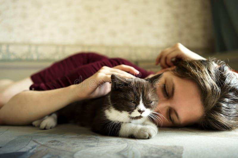 En kvinna och en liten svartvit brittisk kattunge ligger på soffan arkivbild