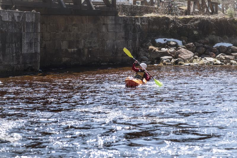 En kvinna på en bergflod kopplas in, i rafting En flicka kayaking ner en bergflod flicka i en kajak, sidosikt royaltyfria bilder