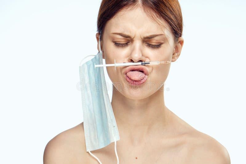 En kvinna på hennes kanter rymmer en injektionsspruta royaltyfria foton