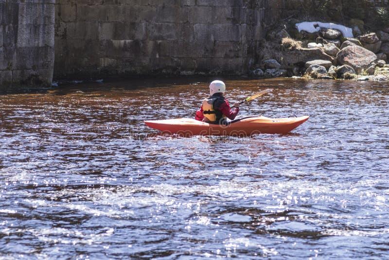 En kvinna p? en bergflod kopplas in, i rafting En flicka kayaking ner en bergflod flicka i en kajak, sidosikt arkivbilder