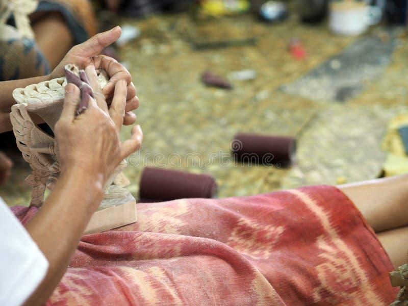 En kvinna polerar en trästatyett i Bali, Indonesien arkivfoto