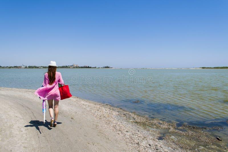 En kvinna promenerar en öde strand som lämnar spår arkivfoton