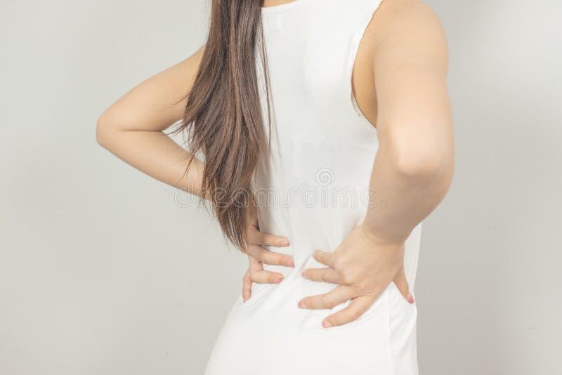 En kvinna rymde hennes hand bak honom med baksida smärtar vart begreppshanden har den sena pillen f?r sjukv?rdhj?lp arkivfoto