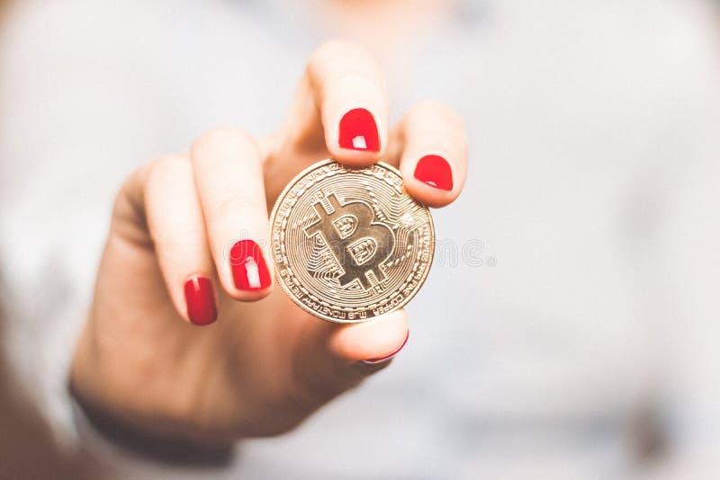 En kvinna rymmer ett guld- mynt i hennes handbitcoin Elektroniska faktiska pengar royaltyfri bild