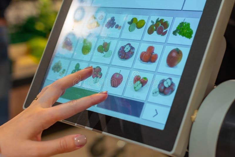 En kvinna söker efter en lämplig frukt på skärmen med elektroniska saldon för vägning arkivfoton