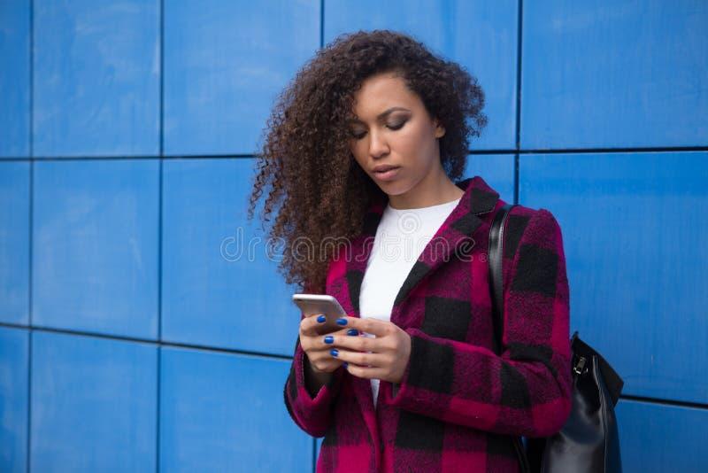 En kvinna ser hennes telefon med avsmak med arkivbild