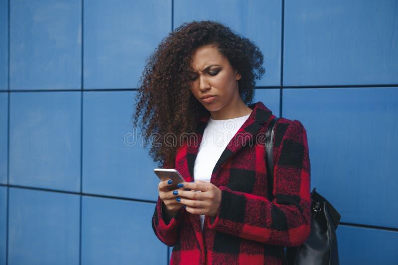 En kvinna ser hennes telefon med avsmak royaltyfria foton