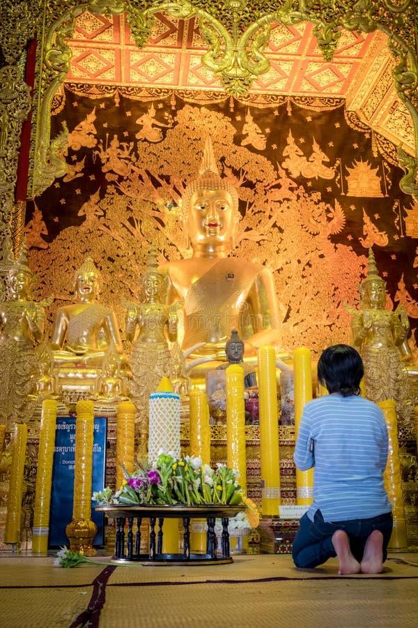 En kvinna sitter f?r att be framme av den guld- Buddhastatyn av Thailand templet namngav ?Wat Den Salee Sri Muang Gan Wat Ban Den arkivbilder