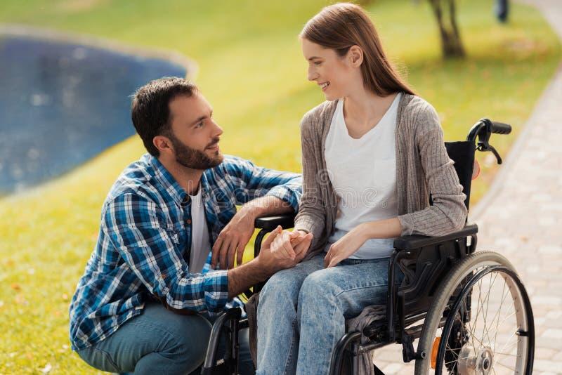 En kvinna sitter i en rullstol En man sitter bredvid hennes och rymmer henne händer arkivfoton