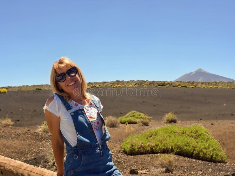 En kvinna sitter på enstam, henne bär solglasögon, den vita skjortan och blåa korta grova bomullstwillar, blont långt hår arkivbilder