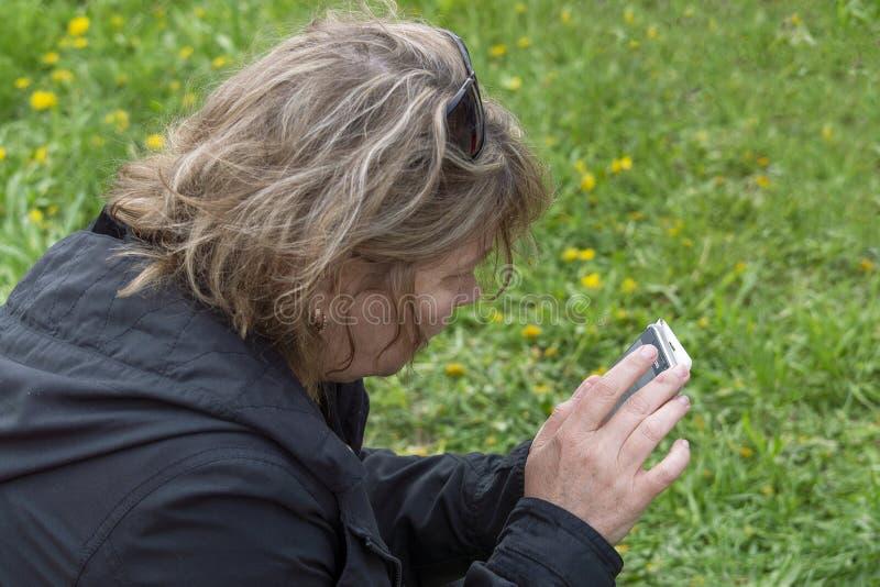 En kvinna sitter på ett grönt gräs och blickar in i den smartphone-, baksida- och sidosikten royaltyfri foto