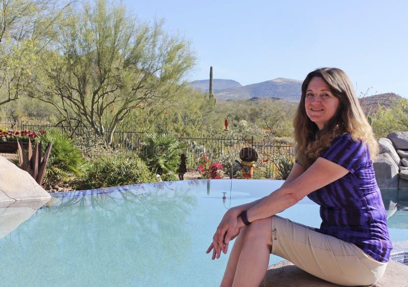 En kvinna sitter poolsiden i öken för Arizona ` s Sonoran royaltyfri bild