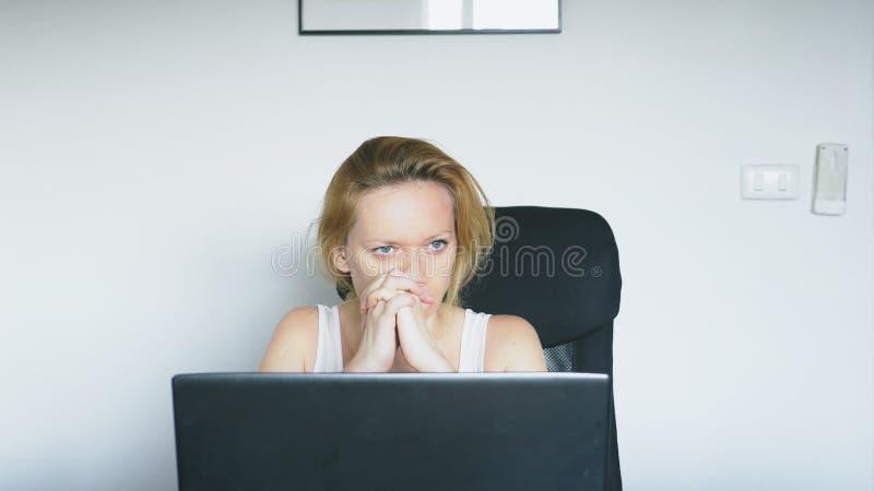 En kvinna som använder en bärbar dator, sitter på tabellen, känner förtvivlan och börjar att gråta mänskliga sinnesrörelser böjel royaltyfria bilder