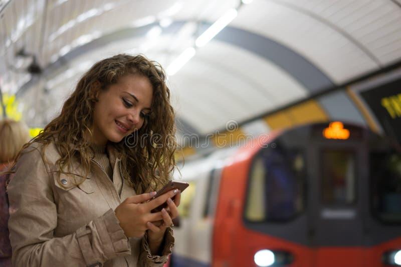 En kvinna som använder en mobiltelefon på den underjordiska stationen för rör, Lo royaltyfri bild