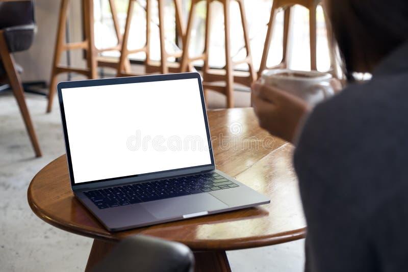 En kvinna som använder och ser bärbara datorn med den tomma vita skrivbords- skärmen, medan dricka varmt kaffe i kafé fotografering för bildbyråer