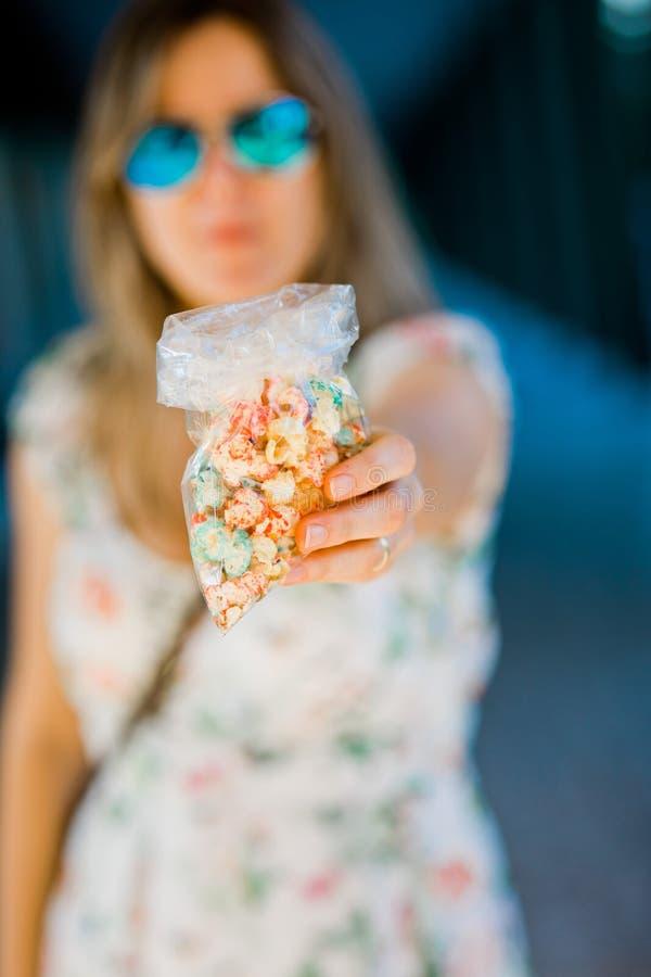 En kvinna som erbjuder s?tt popcorn royaltyfri bild
