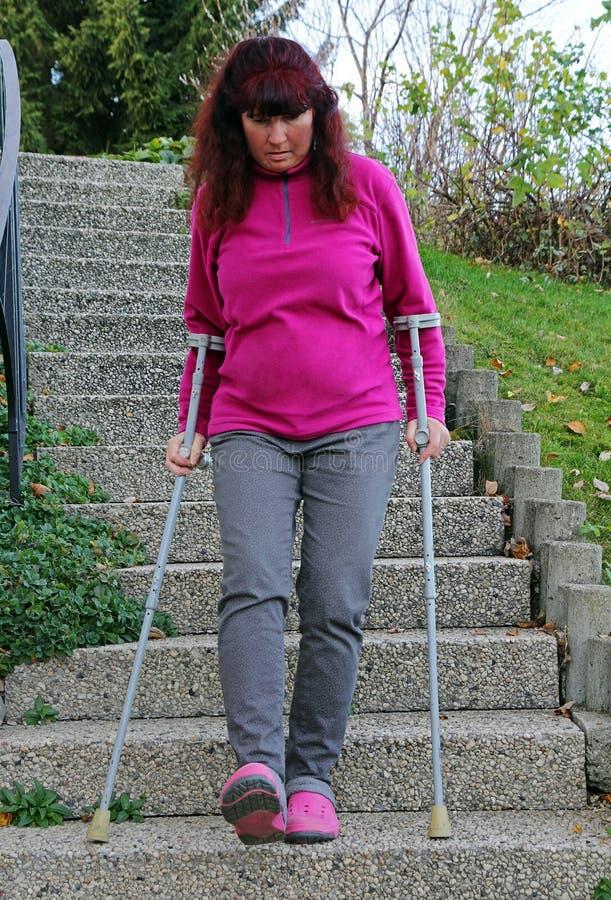 En kvinna som går ner en trappuppgång med kryckor royaltyfri foto