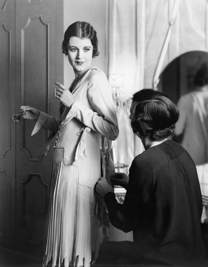 En kvinna som hjälper en annan kvinna som får klädd (alla visade personer inte är längre uppehälle, och inget gods finns Leverant arkivfoto