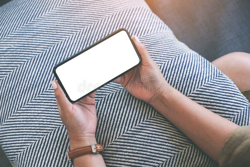En kvinna som horisontellt rymmer den svarta mobiltelefonen med den vita skrivbords- skärmen för mellanrum, medan sitta i varda fotografering för bildbyråer