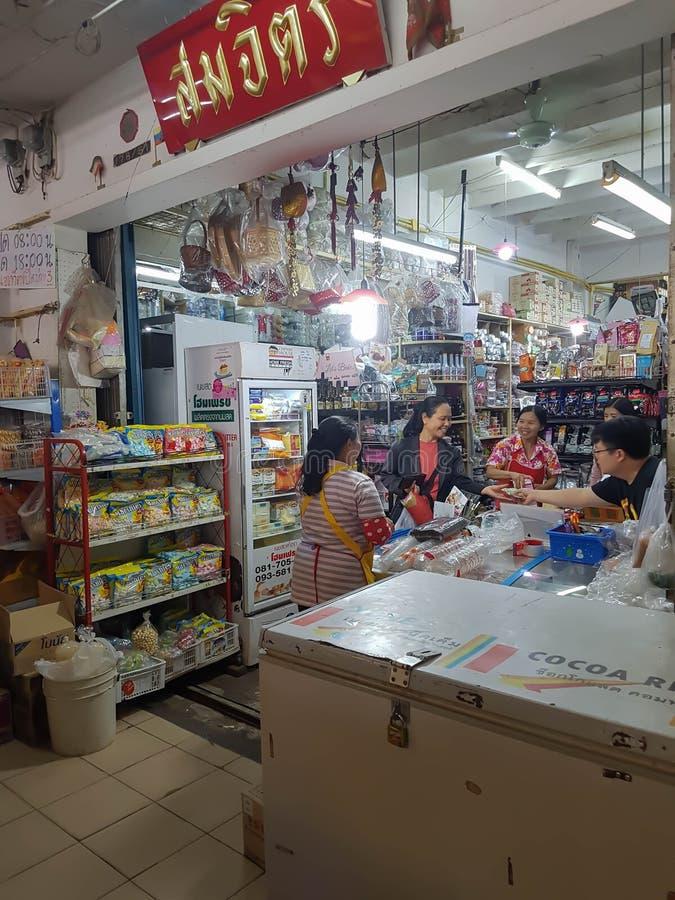 en kvinna som köper någon förbrukningsartikel i gammal gata för specerihandlare` s, shoppar arkivbild