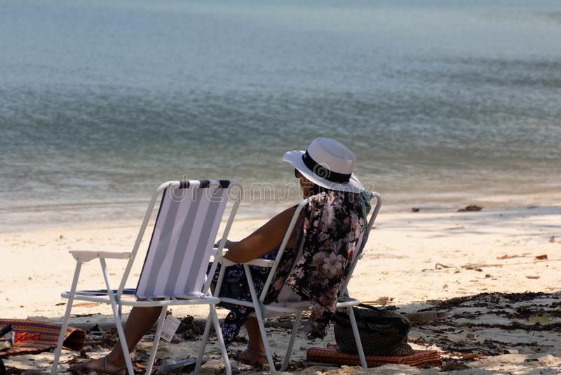 En kvinna som kopplar av på en vit sandig tropisk strand arkivfoto