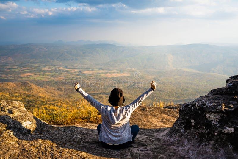 En kvinna som ner sitter med händer upp på det steniga berget som ut ser på den sceniska naturliga sikten och härlig blå himmel arkivfoto