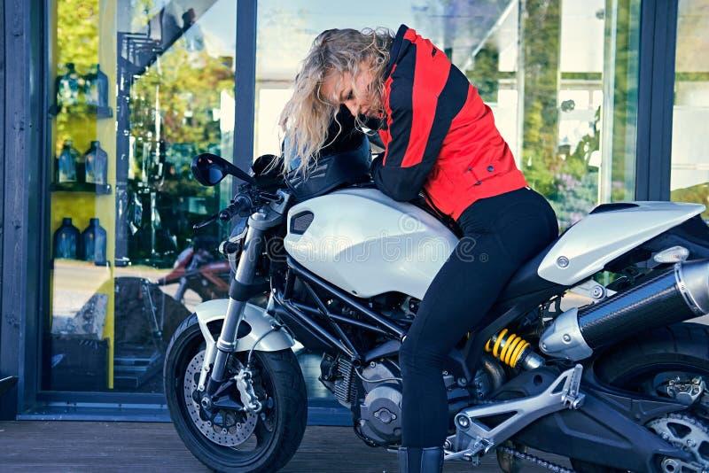 En kvinna som poserar med den vita hastighetsmotorcykeln arkivbilder