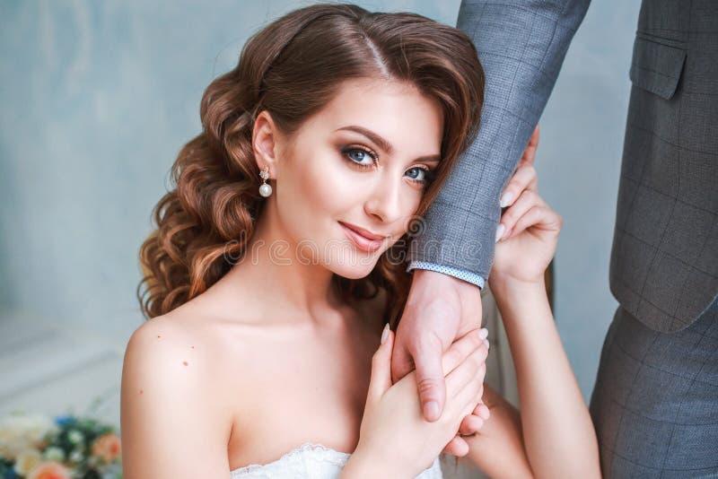 En kvinna som rymmer en hand för man` s Bruden i l klänning och brudgum i grå färger passar ndoors i den vita studioinre royaltyfri fotografi
