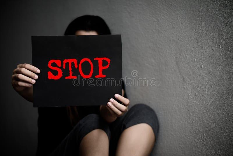 En kvinna som rymmer ett begreppsmässigt stopptecken på våld mot kvinnor royaltyfri bild