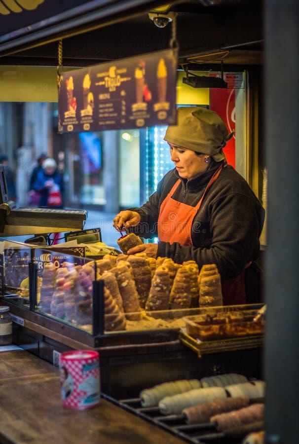 En kvinna som säljer traditionell tjeckisk mat 'trdlo ', royaltyfri foto
