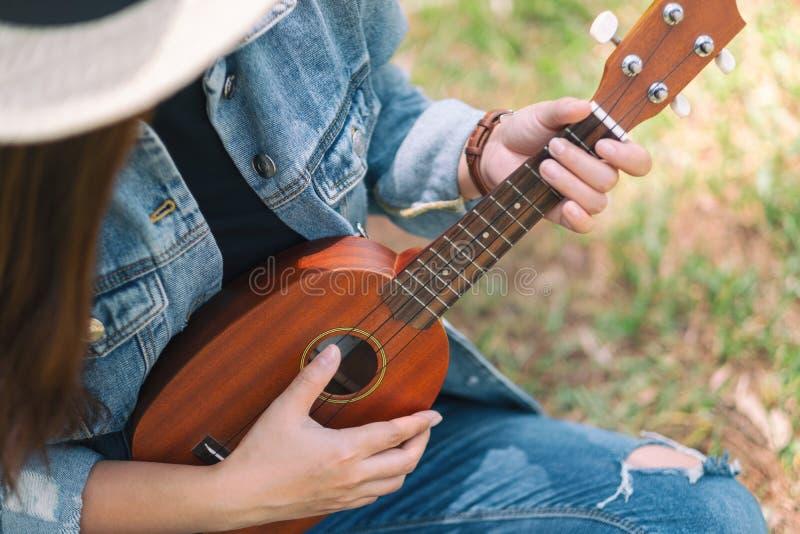 En kvinna som sitter och spelar ukulelet arkivfoto