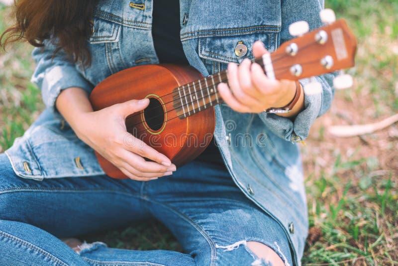 En kvinna som sitter och spelar ukulelet royaltyfri fotografi