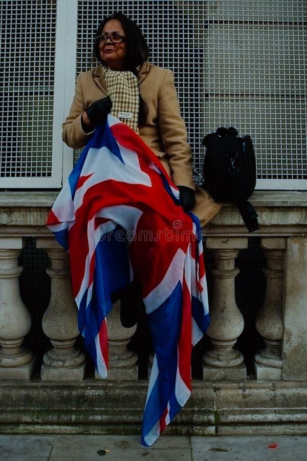 en kvinna som sitter på ett litet snidit staket som rymmer en brittisk flagga under en händelse på staden royaltyfri bild