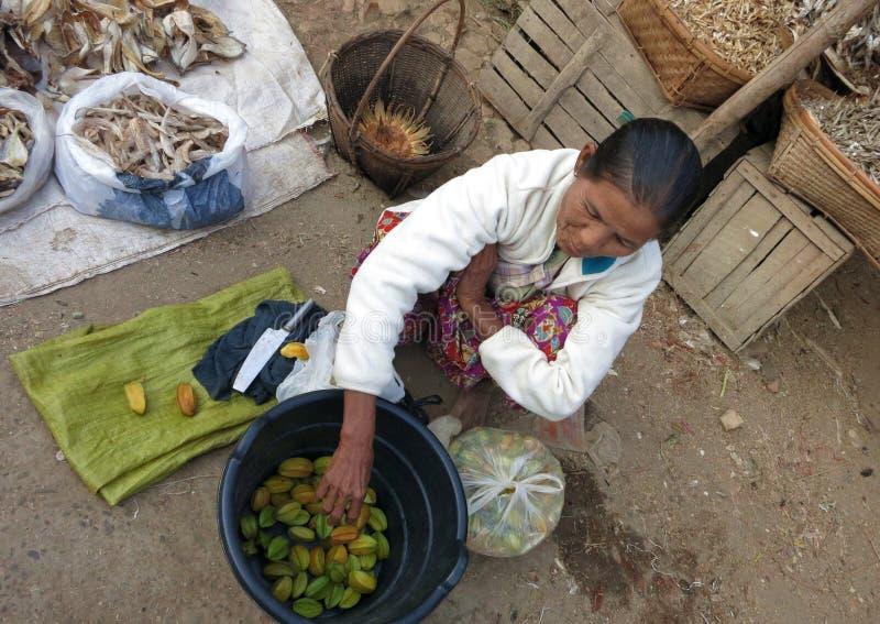 En kvinna som sitter på jordningen, säljer nya starfruits i morgonmarknaden arkivfoto