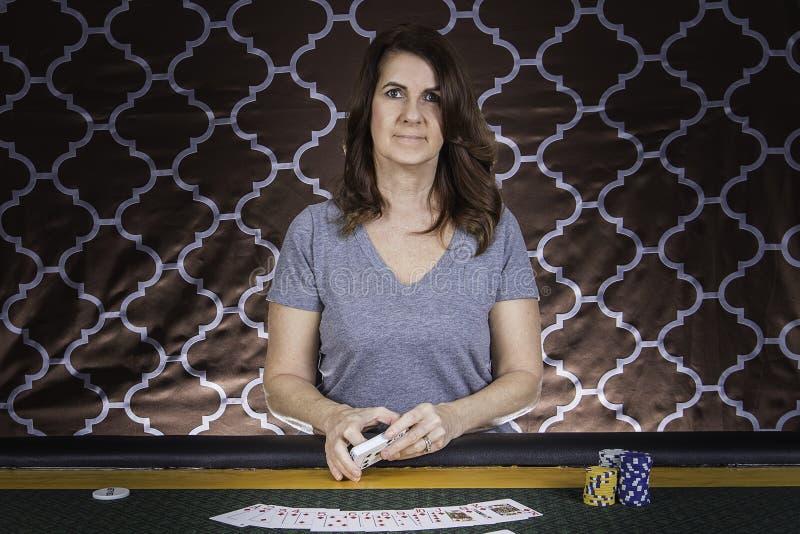 En kvinna som spelar poker på en tabell royaltyfria bilder