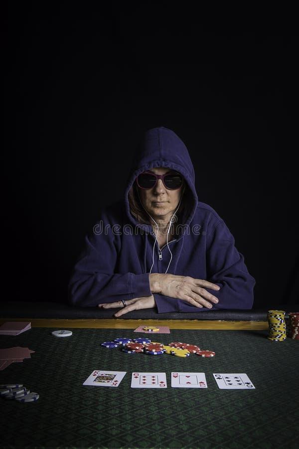 En kvinna som spelar poker på en tabell royaltyfria foton