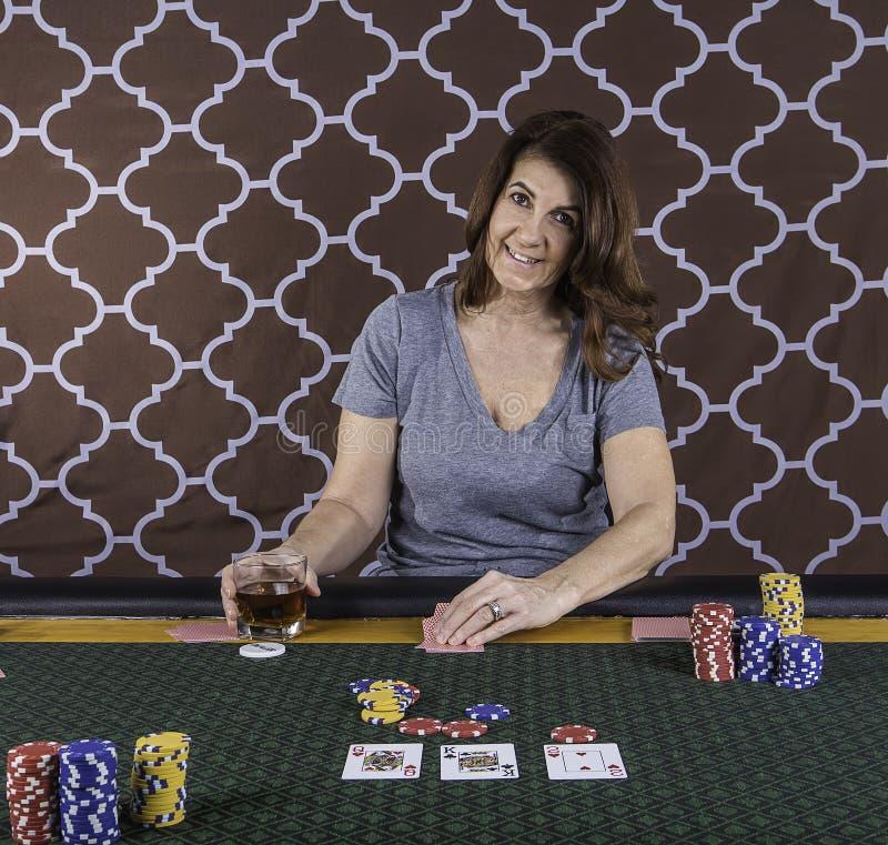 En kvinna som spelar poker på en tabell arkivbilder