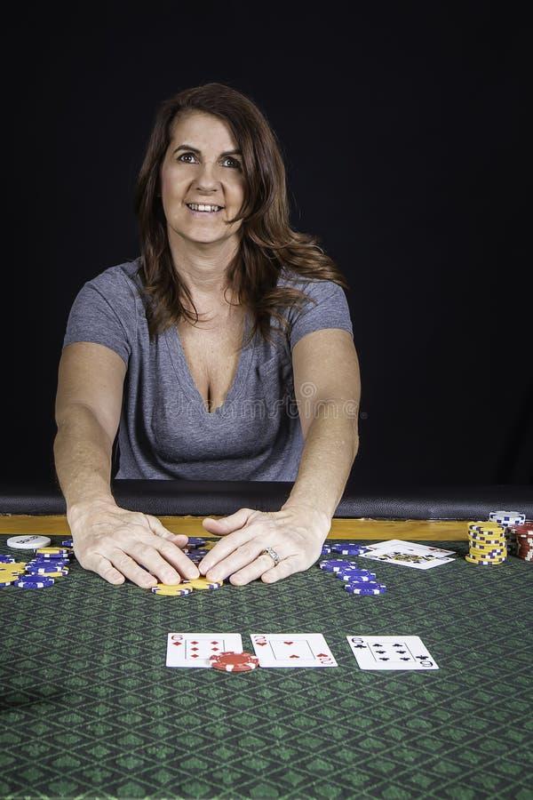 En kvinna som spelar poker på en tabell arkivfoton