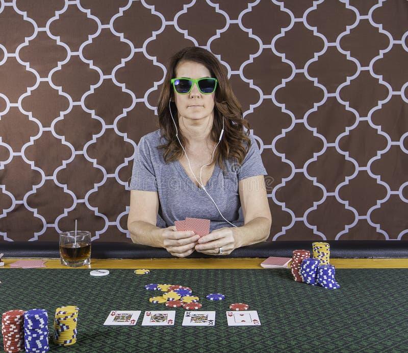 En kvinna som spelar poker på en tabell royaltyfri bild