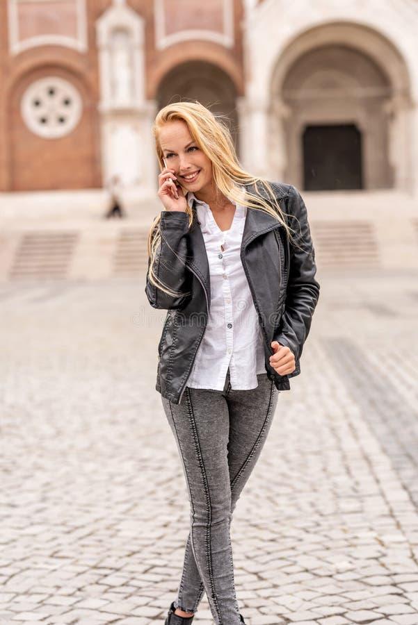 En kvinna som talar på hennes telefon, medan stå på en fyrkant royaltyfri fotografi