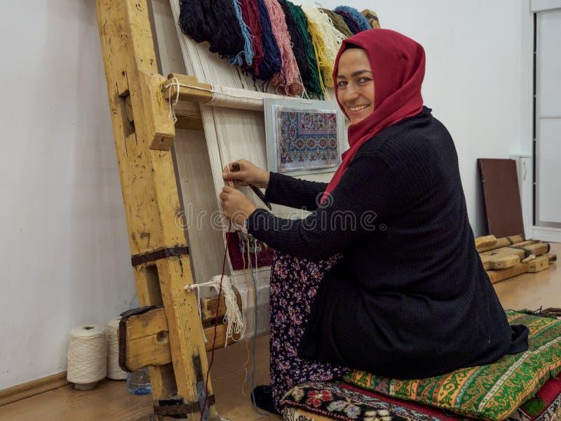 En kvinna som väver den traditionella turkiska mattan arkivbilder
