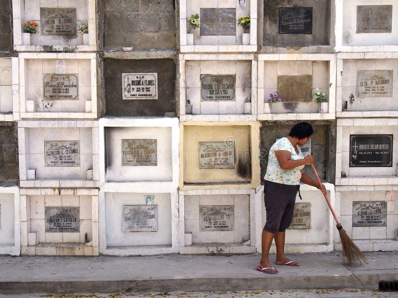 En kvinna sopar framme av kolonner av gravar i en kyrkogård i den Antipolo staden, Filippinerna royaltyfri bild
