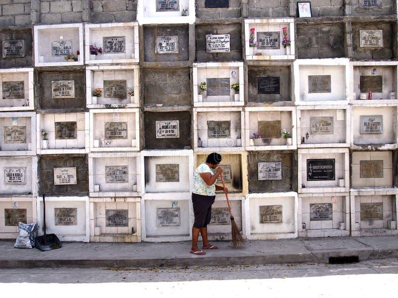 En kvinna sopar framme av kolonner av gravar i en kyrkogård i den Antipolo staden, Filippinerna royaltyfria bilder