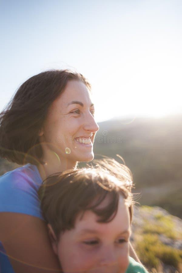 En kvinna spenderar tid med ett barn i natur på solnedgången fotografering för bildbyråer