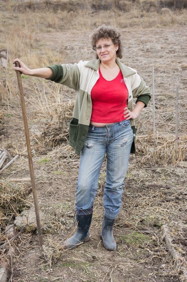 En kvinna står i trädgården, med krattar i hennes händer, mot bakgrunden av torrt gräs arkivbilder