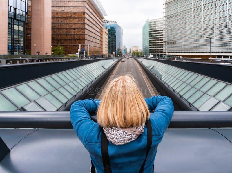 En kvinna står på en bro med ryggen till kameran mot bakgrund av ett modernt kontorshalvår, Belgien royaltyfria bilder