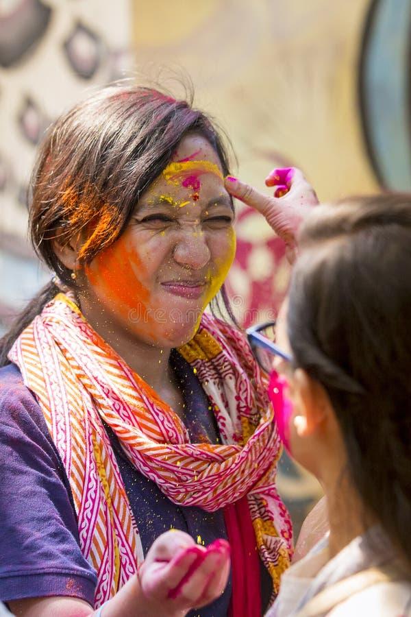 En kvinna suddig med kulört pulver, tagande särar i berömmar av den Dol Utsav festivalen arkivfoton