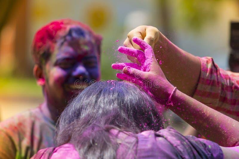 En kvinna suddig med kulört pulver, tagande särar i berömmar av den Dol Utsav festivalen, en festival av den hinduiska gemenskape royaltyfri fotografi