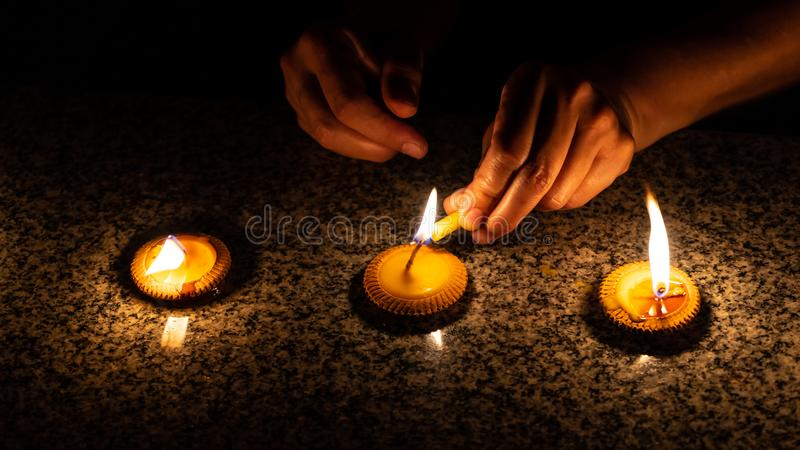 En kvinna tänder tre thailändska utformade stearinljus under den Loy Krathong eller Yeepeng festivalen i Chiang Mai royaltyfri foto