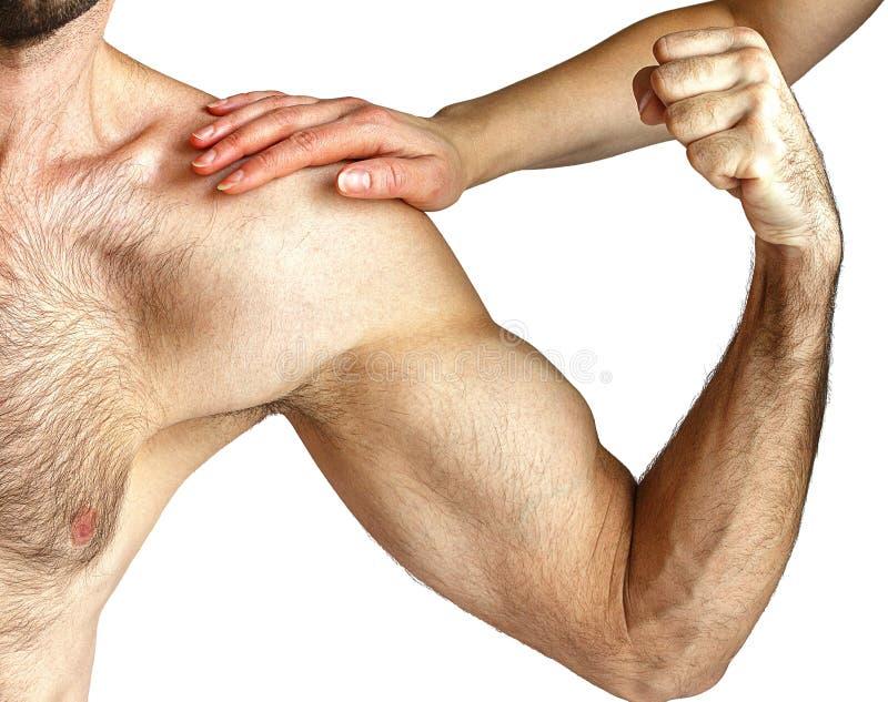 En kvinna trycker på muskler för man` ett s arkivbild